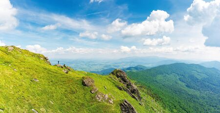 rock on the edge of a hill. view in to the valley. beautiful summer landscape of carpathian mountains. grass on the slope beneath a cloudy sky. borzhava ridge on the horizon, location mnt. pikui, UA