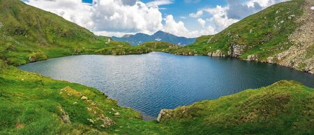 lake capra of romanian fagaras massif panorama. beautiful alpine scenery of carpathians in summer. clouds on the blue sky. grass and boulders on the slopes