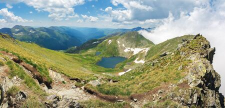 lake capra of romanian fagaras massif view from the top. beautiful alpine panorama of carpathians in summer. clouds on the blue sky. grass and boulders on the slopes 写真素材