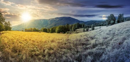 day and night time change in mountains. panorama with beech trees on the grassy meadow. ridge in the distance beneath a sky with sun and moon Stock Photo