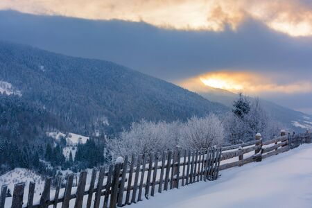 rural countryside in winter. beautiful sunrise with cloudy sky in mountains. wooden fence along the snow covered hill. trees in hoarfrost