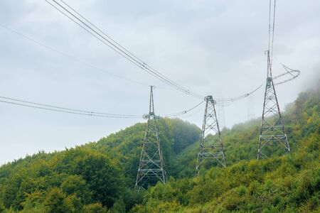 high voltage power lines tower in mountains.  energy delivery background. efficient electricity delivery concept. hazy weather with overcast sky Banco de Imagens