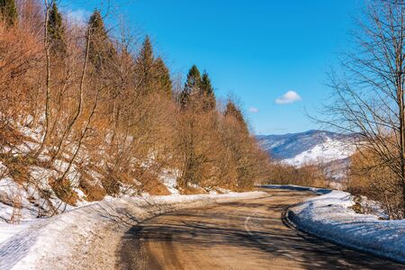 serpentine way in mountains. winding road on a sunny winter day. old cracked asphalt surface. snow on the road sine and hills of the ridge in the distance. leafless trees along the path