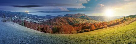 day and night time change concept above panoramic landscape in october. grassy meadow and trees in fall foliage. mountain range in the distance beneath a sun and moon on the sky