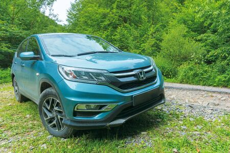 mnt. runa, ukraine - jun 22, 2019: dirty honda crv near the old cracked road through beech forest. 4th generation of a popular family SUV, restyling model 2015 in cyan blue color.