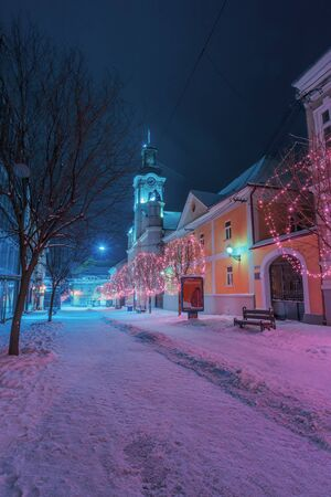 uzhgorod, ukraine - 06 JAN, 2019: winter night in town. wonderful blue and purple christmas illumination. empty Voloshyna street covered in snow. catholic Cathedral in the distance Editorial