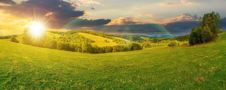 panoramic mountain landscape at sunset. grassy meadow on the hillside in evening light. trees on the edge of a hill. mountain ridge in the distance. clouds on the sky