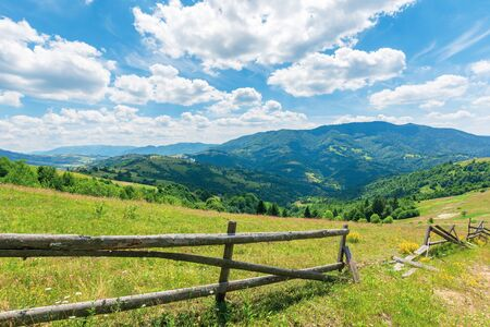 wonderful landscape of rural area at noon.  amazing cloudscape above the distant mountain ridge. beautiful sunny weather. wooden fence on the grassy meadow Stock Photo