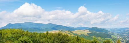 beautiful countryside in mountain. sunny weather. clouds on the blue sky. lovely panoramic landscape with ridge and village in the valley Stock Photo