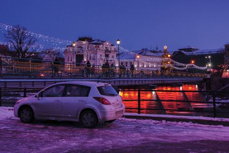 uzhgorod, ukraine - 06 JAN, 2019: winter dawn in town. wonderful urban scenery with city light on the bridge and christmas tree in the distance. dirty car nissan tiida parked on the embankment Editorial