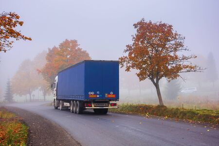transcarpathia, ukraine - oct 09, 2018: truck on the serpentine in fog. breaking before the road turn. trees in fall foliage. sneaky autumn weather. deceptive nature beauty concept. Editorial