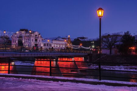 uzhgorod, ukraine - 06 JAN, 2019: winter dawn in town. wonderful urban scenery with city light on the bridge and christmas tree in the distance. lantern on the embankment