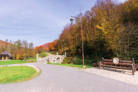 beautiful park in the mountains. wonderful sunny autumn weather. trees in fall foliage. lanterns and benches along the walking path, blue sky with clouds Stock Photo
