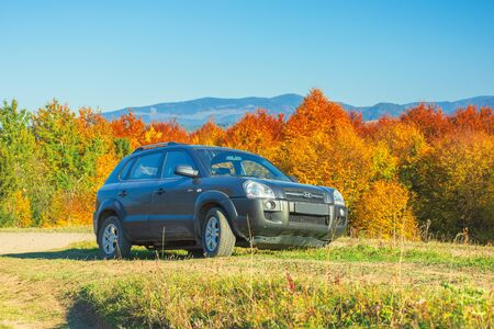 Mizhhirya, Ukraine - OCT 14, 2018: Hyundai Tucson suv on the gravel country road side in mountains. trees in colorful fall foliage on the background. ridge in the distance. travel by car concept