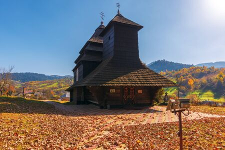 Uzhok, Ukraine - OCT 18, 2018: Church of the Archangel Michael - UNESCO World Heritage. old wooden building in mountains. wonderful sunny autumn weather. trees in fall foliage. cloudless sky Editorial