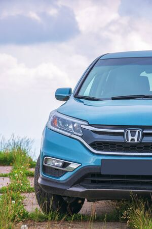 mnt. runa, ukraine - jun 22, 2019: honda cr-v suv on a paved platform in mountains. popular family vehicle, in cyan blue color. cloudy day and even light. explore back country by car