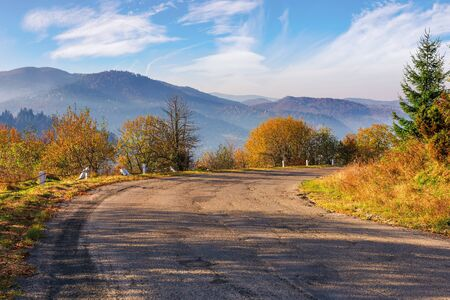 old serpentine road in mountains. beautiful autumn scenery in morning misty light. wonderful october weather with fluffy clouds on the sky. ridge in the distance