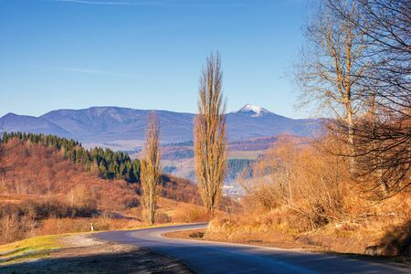 road winding in mountains in autumn. beautiful autumn scenery in morning light. wonderful november weather. ridge in the distance with snow covered peak Stock Photo