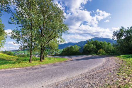 serpentine road in mountains. beautiful scenery in evening light. wonderful september weather with fluffy clouds on the sky. trees on grassy meadow along the path. range in the distance Stock Photo