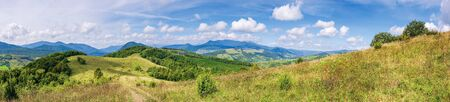 wonderful autumn mountain panorama. pikui peak of watershed ridge beneath clouds. trees on grassy rolling hills. wonderful carpathian countryside on a sunny day of september.
