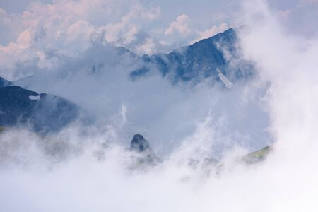 stunning scenery of cloud formations in high mountains of romania. fagaras ridge in dynamic weather condition. beautiful nature background. dreams in the air concept