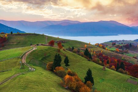 wonderful autumn countryside in mountains at dawn. valley full of floating cold fog. glowing sky above the distant ridge. country road rolling along the hills of rural area. Stock Photo