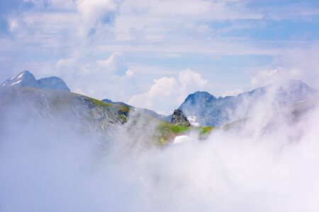 stunning scenery of cloud formations in high mountains of romania. fagaras ridge in dynamic weather condition. beautiful nature background. dreams in the air concept Stock Photo - 129127362