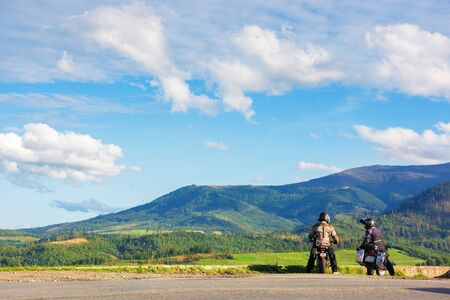 volovets, ukraine - SEP 15, 2017: two motorcyclist on the road enjoying alpine scenery. beautiful mountain landscape with wonderful cloudscape in evening light. borzhava ridge in the distance Stock Photo - 137010169