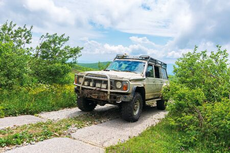 mnt. Runa, Ukraine - JUN 19, 2019: old off road vehicle on the paved mountain road. dirty SUV prepared for the battle with nature. mountain in the distance beneath a cloudy sky