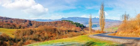 sunny morning in mountainous countryside. panorama of ukrainian carpathian rural area in november. leafless trees on hills and along the road bend. ridge with snow capped pikui peak in the distance Stock Photo