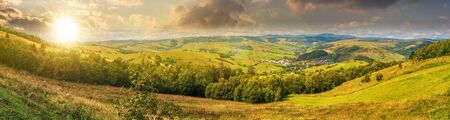beautiful countryside panorama in autumn at sunset. grassy hills and meadows. trees with green foliage on hillsides. mountain ridge in the distance. wonderful nature scenery of Carpathians