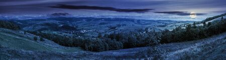 panorama of mountainous countryside at night in full moon light. beautiful highland landscape with grassy fields. row of trees along the hill. rural area in the distance