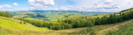 panorama of a countryside in early autumn. village on the hillside, mountain ridge in the distance. sunny weather with clouds on the sky. view from the hill. Stock Photo