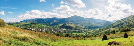 wonderful carpathian countryside in the afternoon. sunny weather with fluffy clouds on the sky. beautiful rural landscape in early autumn. great panorama of borzhava mountain ridge in the distance.