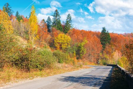 country road through forest in mountains. beautiful transportation autumn scenery in the morning. trees in colorful foliage. concrete border along the old cracked asphalt surface. clouds on the blue sky