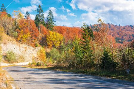 country road through forest in mountains. beautiful transportation autumn scenery in the morning. trees in colorful foliage. old cracked asphalt surface needs repair. clouds on the blue sky