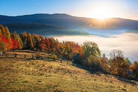 amazing countryside in fall season at sunrise. gorgeous view in to the valley full of fog in morning light. sun above the distant mountain. fence through rural field on the hillside. beautiful autumn