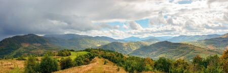 panoramic mountain landscape in autumn. colorful scenery on a sunny day. changing weather with clouds on the sky. abandoned footpath down the hill. distant ridge in haze. travel back country concept