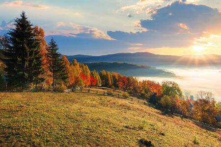 amazing countryside in fall season at sunrise. gorgeous view in to the valley full of glowing fog. sun above the distant mountains. fence through rural field on the hillside. beautiful autumn landscape