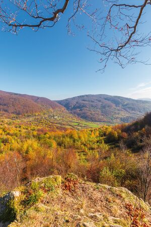 autumn scenery in mountains on a sunny day. view from a high vantage point in to the distant valley. trees in colorful foliage. rail station and viaduct in the distance. abandoned place Stock Photo