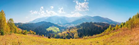 panorama of borzhava mountain ridge. beautiful autumn landscape of carpathians. calm sunny weather with fluffy clouds on a bright blue sky. village in the distant valley