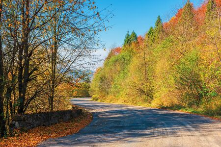old asphalt road in mountains. path along the forest on hill. trees in fall colors. distant ridge in haze. sunny autumn weather with fluffy clouds on the bright blue sky
