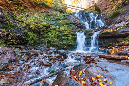 waterfall Shypot of Carpathian mountains in autumn. powerful stream of water. brown foliage on the rocks