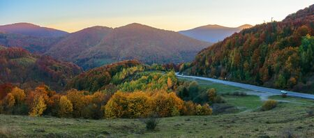 wonderful countryside in mountains at dusk.  serpentine road runs down in to the valley. trees on hills in colorful fall foliage. beautiful autumn panorama of carpathians