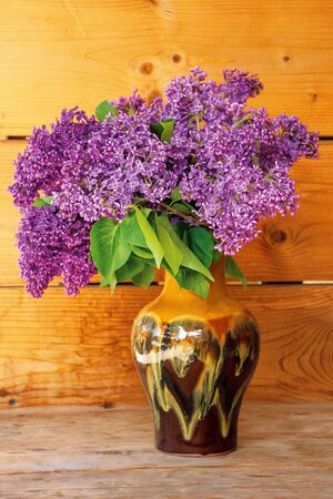 lilac branches in a vase on the wooden base. beautiful spring still life.