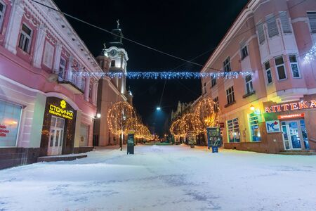 uzhgorod, ukraine - 06 JAN, 2019: winter night in town. wonderful blue and yellow christmas illumination. empty Voloshyna street covered in snow. catholic Cathedral in the distance