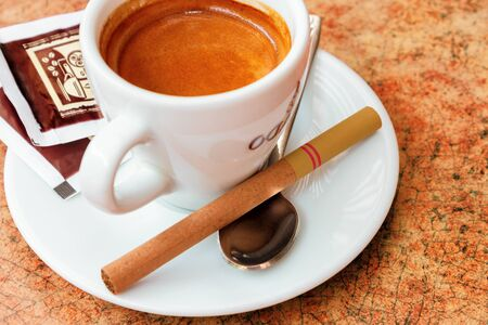 uzhhorod, ukraine - 27 APR, 2013. cup of coffee and small cigar on the table. cute bad habits. addiction problem concept