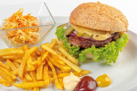fast food menu. hamburger, french fries and salad. burger with beef stake, cheese onion and pickle. mayonnaise ketchup mustard on the white plate. healthy variation of junk food. close up view Stock Photo