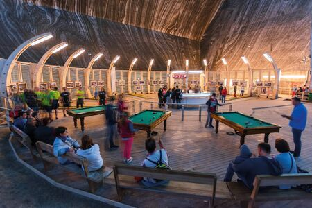 TURDA, ROMANIA - APR 30, 2018: Hall of Salt Mine Salina Turda museum. popular travel destination. underground place with where people rest, have fun playing pool or snooker and recreation. Editorial