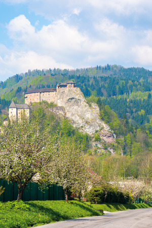 Orava Castle on the high steep rock. one of the most beautiful castles in Slovakia. beautiful sunny day. trees along the road in blossom. popular travel destination